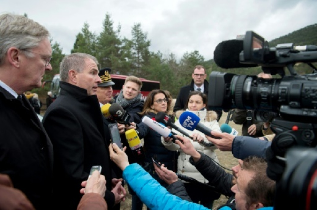 Luftansa CEO Carsten Spohr (2L) and Germanwings former CEO Thomas Winkelmann (L) speak to journalists during the commemoration ceremonies at the Vernet memorial, southeastern France, on March 24, 2017 to mark the second anniversary of th...