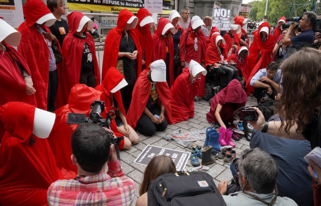 "Women dressed as characters from the novel-turned-TV series ""The Handmaid's Tale"" protest in front of the Alexander Hamilton Customs House on July 31, 2018, in New York, where US Vice President Mike Pence was speaking at a Department of Homeland Security conference. The demonstrators were protesting the immigration and religious policies of the administration of US President Donald Trump. TIMOTHY A. CLARY / AFP"