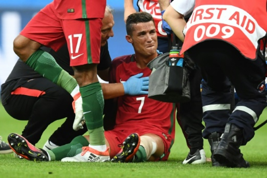 Portugal's forward Cristiano Ronaldo reacts as medics arrive on the pitch during the Euro 2016 final football match between France and Portugal at the Stade de France in Saint-Denis, north of Paris, on July 10, 2016.