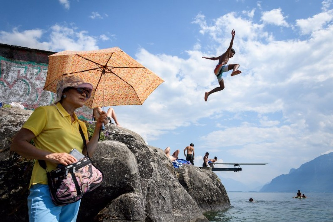 A boy jumps into Geneva Lake in Saint Saphorin, western Switzerland, above a tourist protecting herself from the sun with an umbrella as a heatwave is sweeping across northern Europe on July 31, 2018.  Fabrice COFFRINI / AFP