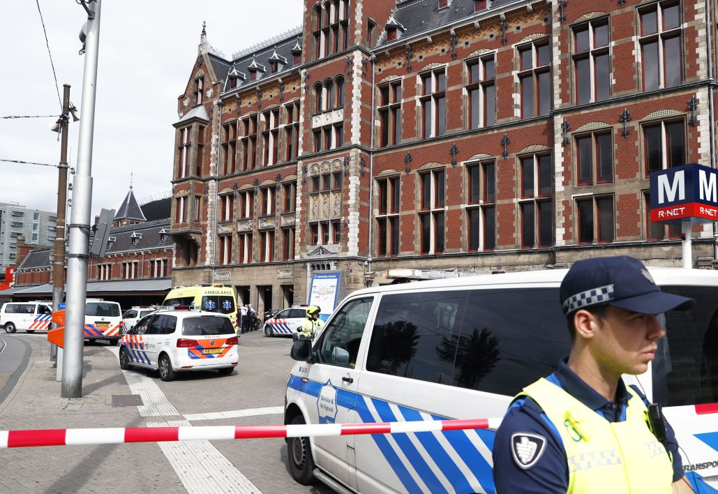 A security official stands beside a cordonned-off area at The Central Railway Station in Amsterdam on August 31, 2018, after two people were injured in a stabbing incident. Two people were hurt during a stabbing incident at Amsterdam's busy Central Station with the alleged attacker shot and wounded, Dutch police said.  Remko de Waal / ANP