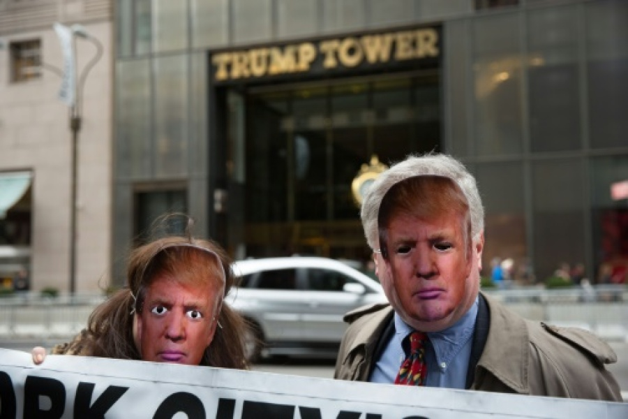 Des personnes portant des masques de Donald Trump, le 1er avril 2017 à New York, devant la Trump Tower