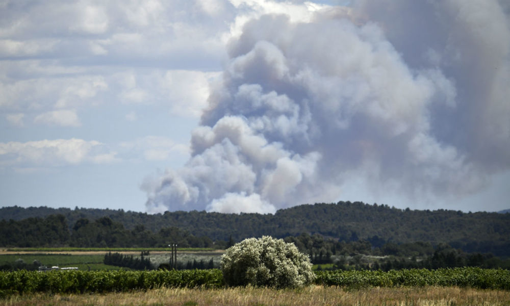 A fire is pictured near the road of the 162,5 km eleventh stage of the 103rd edition of the Tour de France cycling race on July 13, 2016 between Carcassonne and Montpellier. Significant human and material resources were deployed on July 13, 2016 afternoon in the Aude to contain a fire that raged not far from the road of the Tour de France without threatening it, according to firefighters.