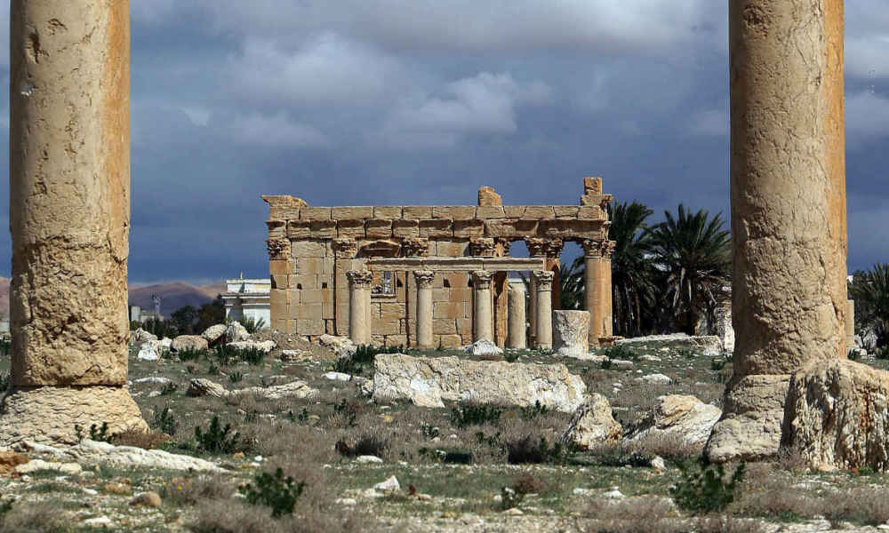 "A picture taken on March 14, 2014 shows the Temple of Baal Shamin seen through two Corinthian columns in the ancient oasis city of Palmyra, 215 kilometres northeast of Damascus. Islamic State group jihadists on August 23, 2015 blew up the ancient temple of Baal Shamin in the UNESCO-listed Syrian city of Palmyra, the country's antiquities chief told AFP. ""Daesh placed a large quantity of explosives in the temple of Baal Shamin today and then blew it up causing much damage to the temple,"" said Maamoun Abdulkarim, using another name for IS. IS, which controls swathes of Syria and neighbouring Iraq, captured Palmyra on May 21, sparking international concern about the fate of the heritage site described by UNESCO as of ""outstanding universal value"". AFP PHOTO/JOSEPH EID"