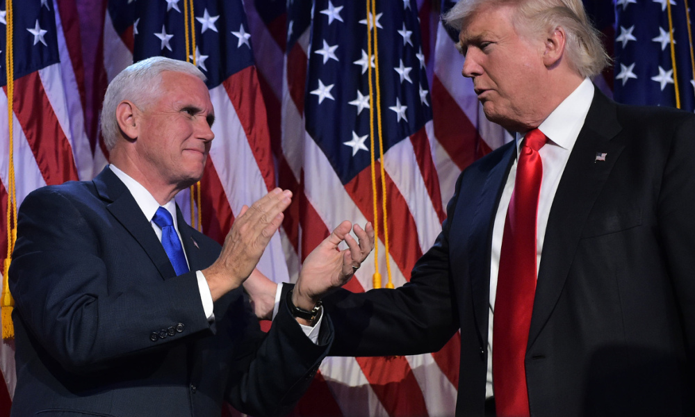 Republican presidential elect Donald Trump (R) reaches to his Vice President elect Mike Pence during election night at the New York Hilton Midtown in New York on November 9, 2016. Trump stunned America and the world Wednesday, riding a wave of populist resentment to defeat Hillary Clinton in the race to become the 45th president of the United States. MANDEL NGAN / AFP