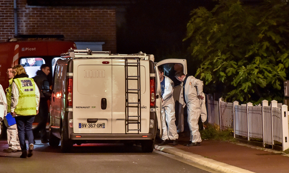 Forensic police and emergency services workers stand outside the house (back L) where five members of the same family were found dead on October 21, 2015 in Haubourdin, in the suburbs of Lille, according to police sources. The bodies of the three children, the youngest of whom was six months old, the mother and the father, who had hanged himself, were found in the family home