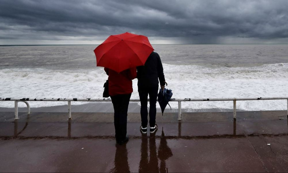 People look at the shore as a storm is approaching, on April 12, 2018 on the French riviera city of Nice.  VALERY HACHE / AFP