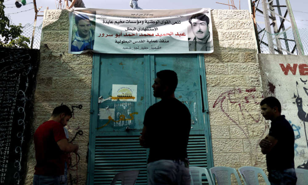 "Palestinian youth stand next to a poster depicting a portrait of Abdel Hamid Abu Sorur (L), 19, at Aida refugee camp in the town of Bethlehem, in the Israeli-occupied West Bank, on April 21, 2016. The 19-year-old died on April 20, two days after an explosive device blew up on a bus in southern Jerusalem and sparked a fire. Israeli police have declined to comment on the specifics of the case, citing an ongoing gag order, including whether Abu Sorur was the attacker. The Islamist movement Hamas, however, did not formally claim the attack, though it hailed him as a martyr and called him ""one of its sons"" -- a term used to refer to Hamas members."