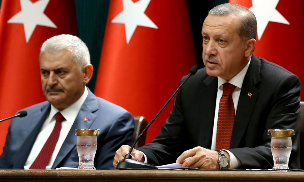 A handout photo released by the Turkish Presidential Press Office shows Turkish President Recep Tayyip Erdogan (R) delivering a speech during a press conference at the Presidential Complex in Ankara on July 22, 2016, flanked by Turkish Prime Minister Binali Yildirim. Turkey imposed a three-month state of emergency on July 21, strengthening state powers to round up suspects behind the failed military coup and suspending a key European rights convention. ADEM ALTAN / TURKISH PRESIDENTIAL PRESS OFFICE / AFP