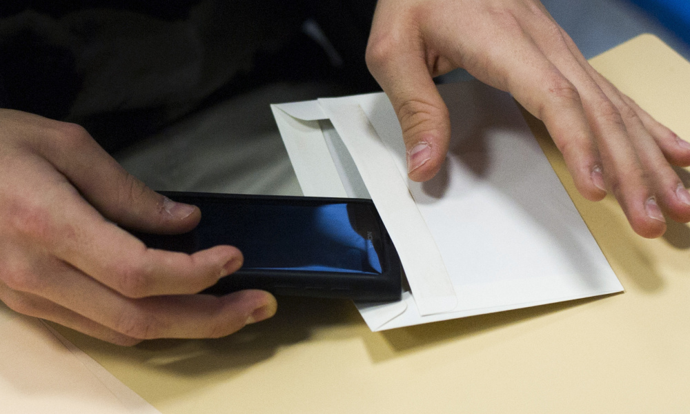 A French student puts his smartphone in an envelope to give it to supervisors before working on the test of philosophy as part of the baccalaureat exam (high school graduation exam) on June 17, 2013 at the Arago high school in Paris. Some 664.709 candidates are registered for the 2013 session. The exam results will be announced on July 5, 2013. AFP PHOTO / FRED DUFOUR FRED DUFOUR / AFP