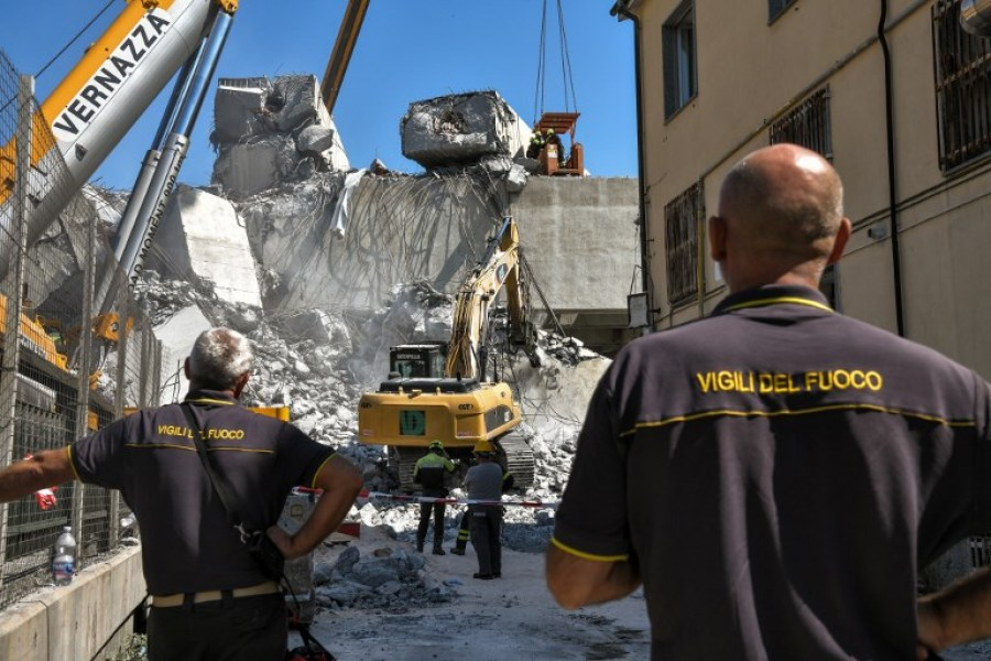 Rescuers inspect the rubble and wreckages at the Morandi motorway bridge, two days after a section collapsed in Genoa on August 16, 2018. A vast span of the Morandi bridge caved in during a heavy rainstorm in the northern port city on August 14, 2018, sending about 35 cars and several trucks plunging 45 metres (150 feet) onto railway tracks below and killing at least 39 people.  Piero CRUCIATTI / AFP