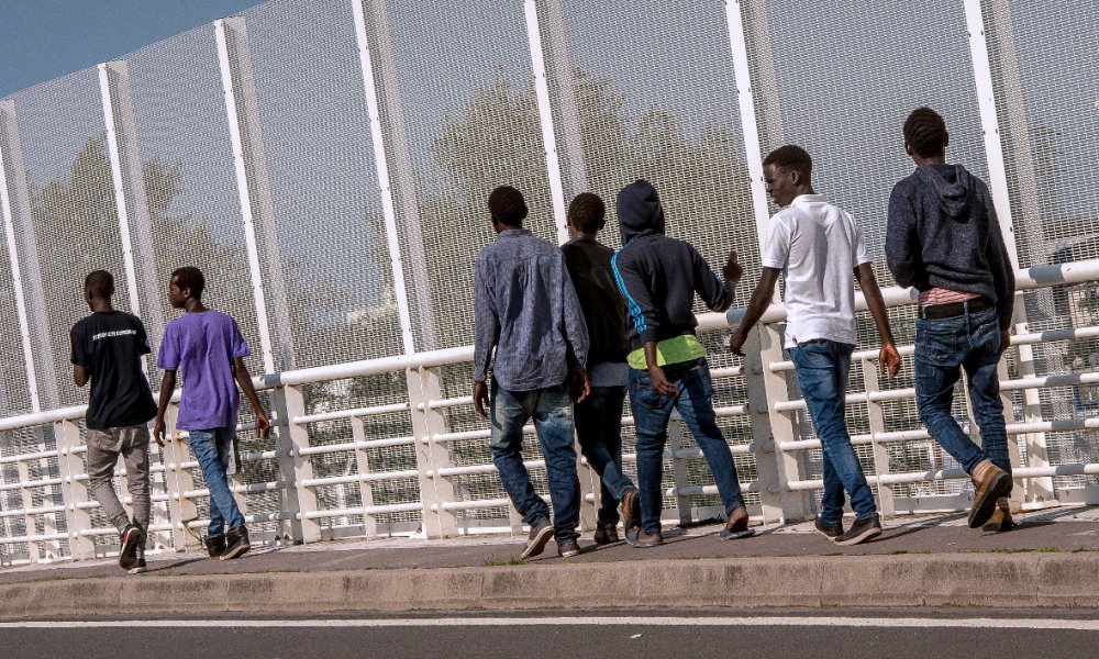 "Migrants walk along a protection fence preventing access to a circular road next to the ""Jungle"" migrant camp in Calais, northern France, on September 8, 2016. Britain is to start building a wall in the northern French port of Calais to stop migrants jumping on trucks, under a deal agreed earlier this year, the interior ministry said on September 7. The four-metre (13-foot) high, one-kilometre long barrier will be built on a port approach road starting this month and should be completed by the end of this year, officials said. PHILIPPE HUGUEN / AFP"