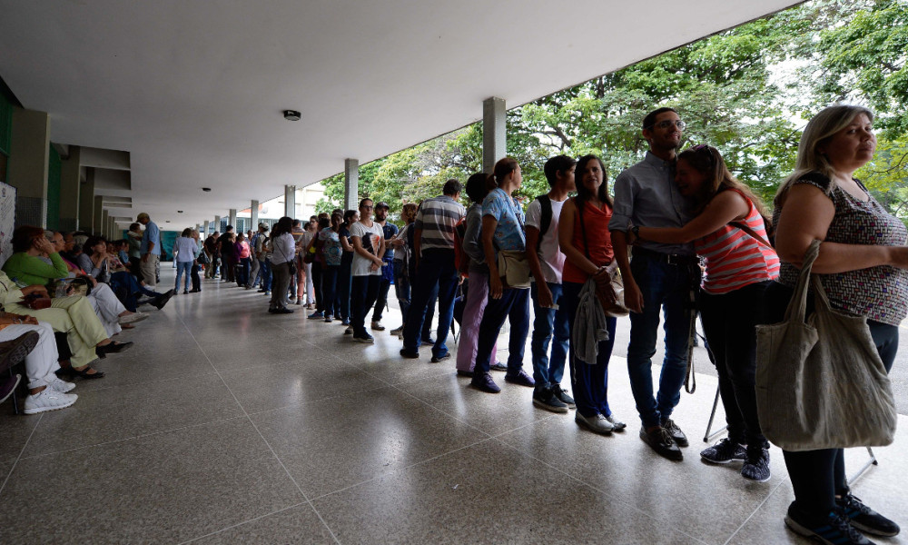Venezuelans line up to authenticate their signatures for a recall referendum before the National Electoral Council (CNE) in Caracas, on June 20, 2016. Venezuelan police have arrested hundreds of people as the country's food crisis erupted into deadly looting this week, heightening hardship and political uncertainty in the impoverished oil-producing nation.