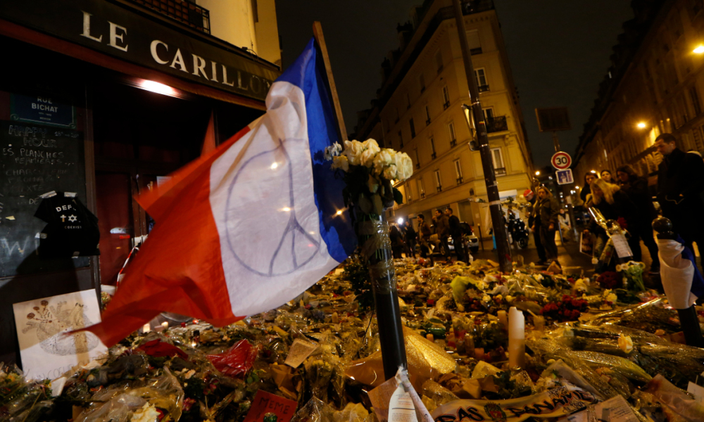 People gather at a makeshift memorial for a tribute to the victims of a series of deadly attacks in Paris, in front of the Carillon cafe on rue Bichat and rue Alibert in Paris on November 20, 2015. Gunmen and suicide bombers went on a killing spree in Paris on November 13, attacking the concert hall Bataclan as well as bars, restaurants and the Stade de France. Islamic State jihadists operating out of Iraq and Syria released a statement claiming responsibility for the coordinated attacks that killed 130 and injured over 350. AFP PHOTO / THOMAS SAMSON  THOMAS SAMSON / AFP