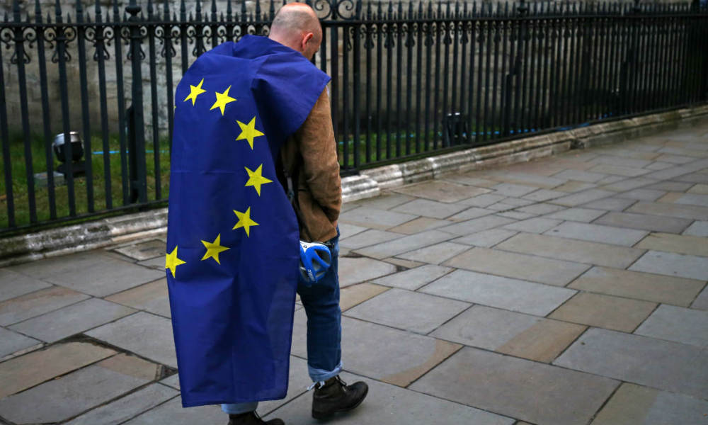 A demonstrator wrapped in a European flag leaves an anti-Brexit protest in central London on June 28, 2016. EU leaders attempted to rescue the European project and Prime Minister David Cameron sought to calm fears over Britain's vote to leave the bloc as ratings agencies downgraded the country. Britain has been pitched into uncertainty by the June 23 referendum result, with Cameron announcing his resignation, the economy facing a string of shocks and