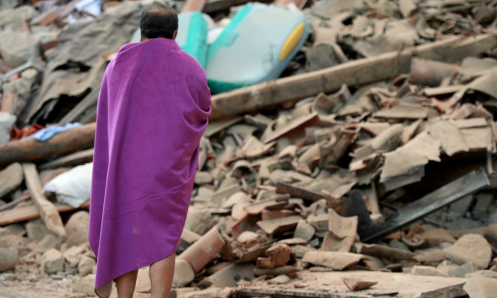 Italie séisme - A man stands among the rubble of a house after a strong heartquake hit Amatrice on August 24, 2016. Central Italy was struck by a powerful, 6.2-magnitude earthquake in the early hours, which has killed at least three people and devastated dozens of mountain villages.
