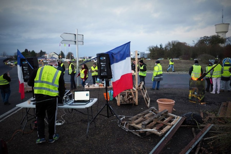 Protestors wearing yellow vests (gilets jaunes) stand at a roundabout to block access to a commercial center in Blois, central France, on November 24, 2018 to protest against rising oil prices and living costs. The protest movement began a week ago when hundreds of thousands of protesters wearing high-visibility yellow vests blockaded roads in a largely spontaneous outpouring of anger about higher diesel taxes. By mid-afternoon on November 24, 81,000 protestors had been counted across France, compared with about 244,000 at the same time last week, figures from the interior ministry showed. Around 8,000 took to the streets in Paris, with about 5,000 on the Champs-Elysees. GUILLAUME SOUVANT / AFP