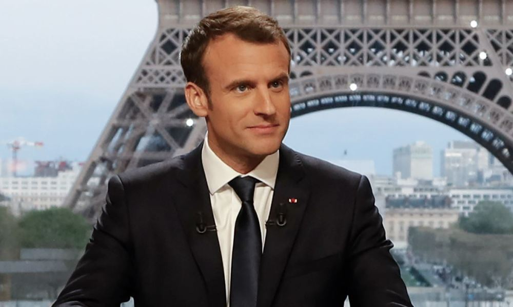 French President Emmanuel Macron (C) poses on the TV set before an interview with RMC-BFM and Mediapart French journalists at the Theatre national de Chaillot in Paris, on April 15, 2018.