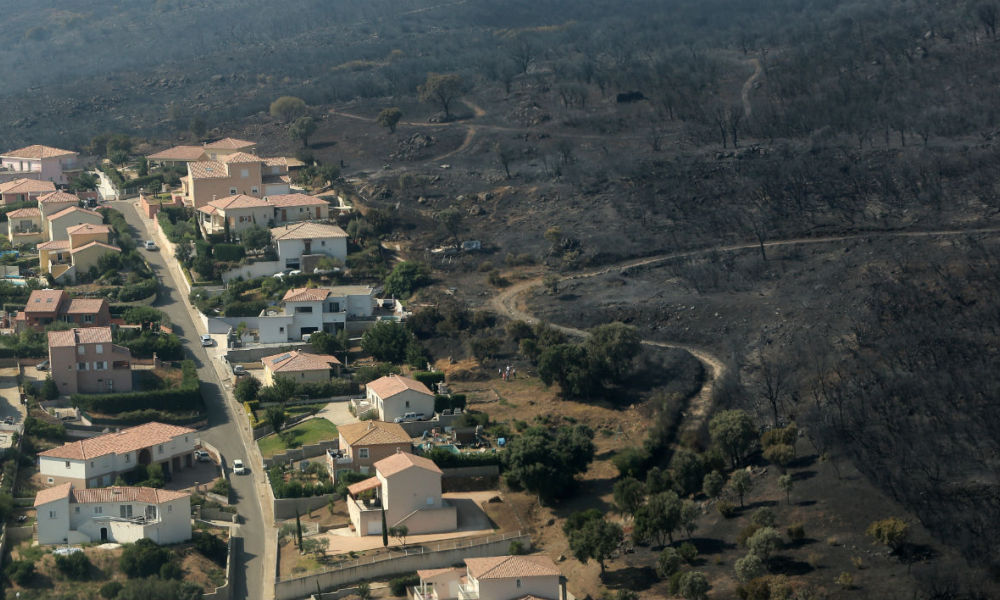 An aerial view taken on July 25, 2017 shows the fire devastated landscape in Biguglia, on the French Mediterranean island of Corsica. France asked for Europe's help on July 25 in fighting wild fires that have consumed swathes of forest in the southeast, one of which is raging near the popular resort of Saint-Tropez. PASCAL POCHARD-CASABIANCA / AFP