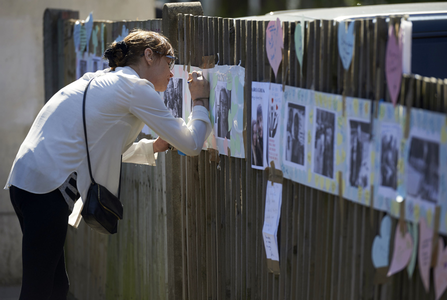 People write tributes on a wall near to the Grenfell Tower block in Kensington, west London, on June 17, following the June 14 fire at the residential building.