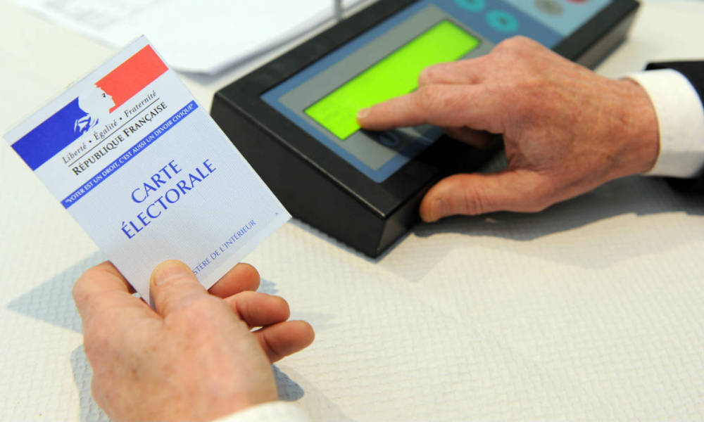 An election volunteer registers an electronic ballot in the first round of the French departementales elections in Brest on March 22, 2015. AFP PHOTO / FRED TANNEAU
