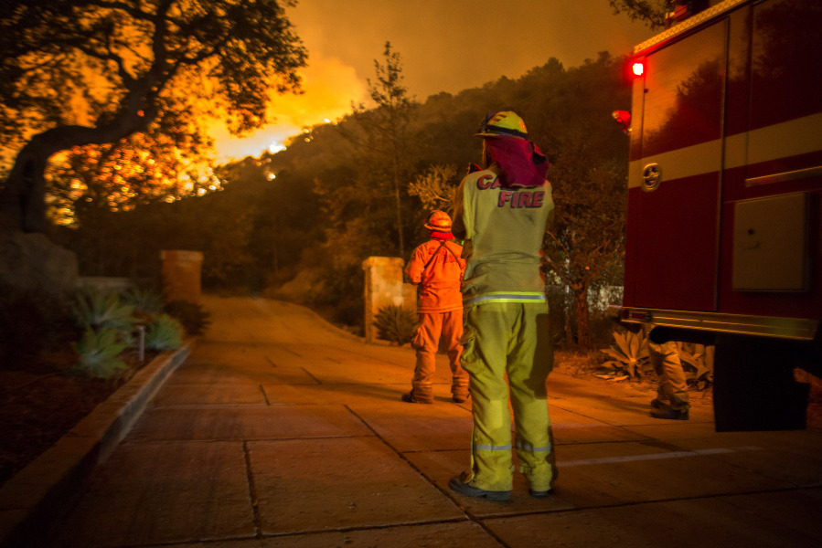 MONTECITO, CA - DECEMBER 12: Firefighters watch flames as the Thomas Fire approaches homes on December 12, 2017 in Montecito, California. The Thomas Fire has spread across 365 miles so far and destroyed about 800 structures since it began on December 5 in Ojai, California. David McNew/Getty Images/AFP