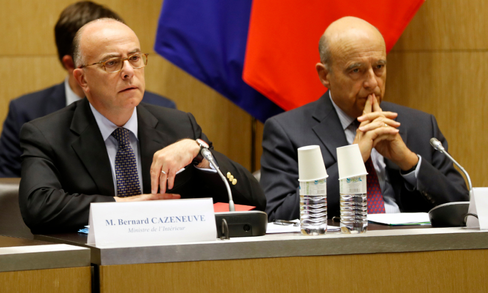 French Interior Minister Bernard Cazeneuve (L) and Mayor of Bordeaux and President of the Association of the Euro 2016 host cities Alain Juppe (R), attend a meeting on the Euro 2016 security measures, on June 8, 2016 at the National Assembly in Paris.  FRANCOIS GUILLOT / AFP