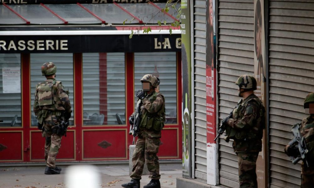 French soldiers stand guard in the northern Paris suburb of Saint-Denis city center, on November 18, 2015, as French Police special forces raid an appartment, hunting those behind the attacks that claimed 129 lives in the French capital five days ago. At least one person was killed in an apartment targeted in the operation aimed at the suspected mastermind of the attacks, Belgian Abdelhamid Abaaoud, and police had been wounded in the shootout. AFP PHOTO / KENZO TRIBOUILLARD