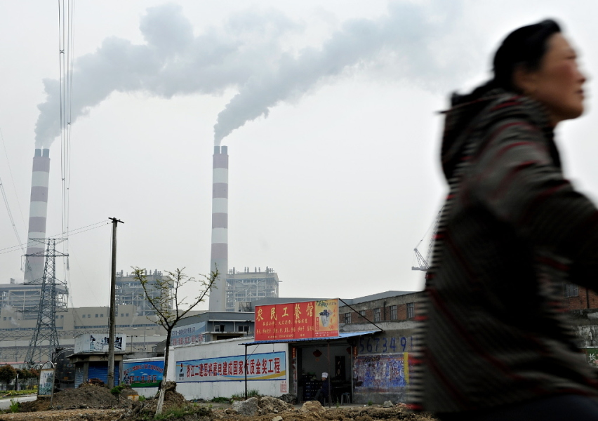 CHINA, Pinghu : A man rides a bicycle past a power plant in Pinghu some 100 kms from Shanghai on April 10, 2010. China posted its first monthly trade deficit in six years in March 2010 as imports rocketed, far outstripping the growth in exports, customs officials announced on April 10, 2010. AFP PHOTO/PHILIPPE LOPEZ