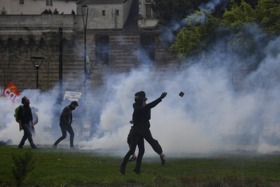 "A protester throws a projectile during clashes with police at a demonstration in support of the Notre-Dame-des-Landes ZAD (Zone a Defendre - Zone to defend) anti-airport camp on April 14, 2018, in Nantes, western France, as a police operation to clear the decade-old camp is ongoing. In January, the government jettisoned plans for an airport that had divided the local community for nearly half a century, and told the protesters to clear off the farmland by spring. But some of the motley group of eco-warriors, anti-capitalists and farmers who had turned the 1,600-hectare (4,000-acre) site into a utopian experiment in autonomous living had demanded the right to stay put. The government said the main aim of the operation was to retake control of a key road that had been blocked for five years and evict around 100 ""of the most radical"" squatters from a total of around 250."