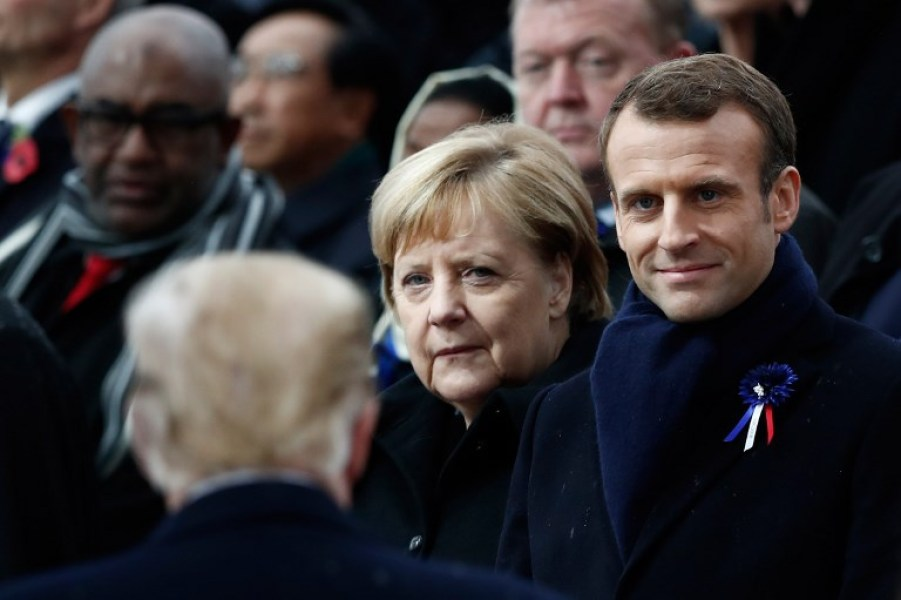German Chancellor Angela Merkel (C) and French President Emmanuel Macron (R) react as US President Donald Trump (front L) arrives to attend a ceremony at the Arc de Triomphe in Paris on November 11, 2018 as part of commemorations marking the 100th anniversary of the 11 November 1918 armistice, ending World War I.  BENOIT TESSIER / POOL / AFP