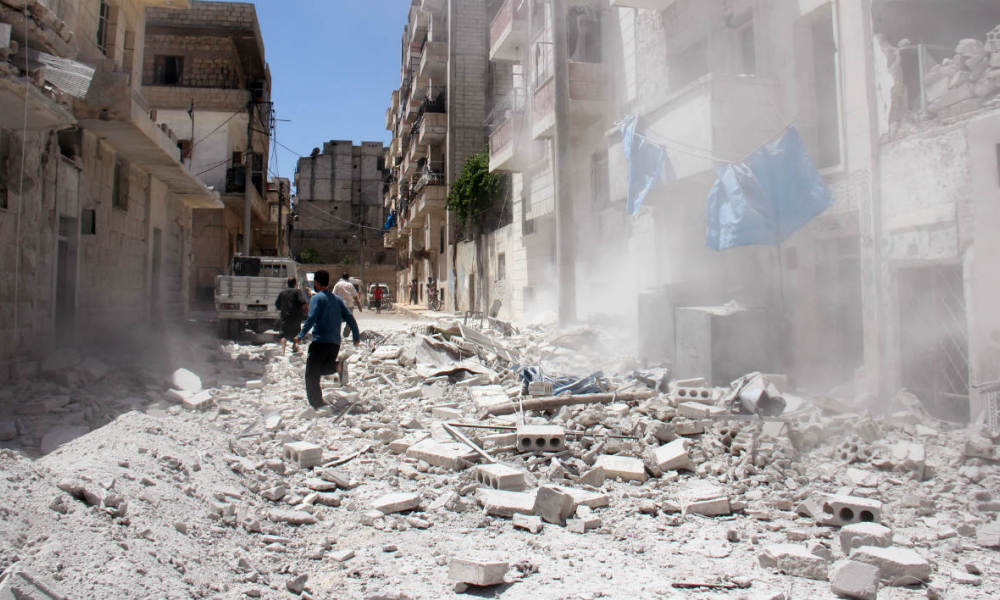 Syrian civilians react following a reported air strike by Syrian government forces on the rebel-held northwestern city of Idlib, on July 20, 2016. More than 280,000 people have been killed and millions displaced since Syria's civil war erupted with the brutal repression of anti-government protests in 2011.