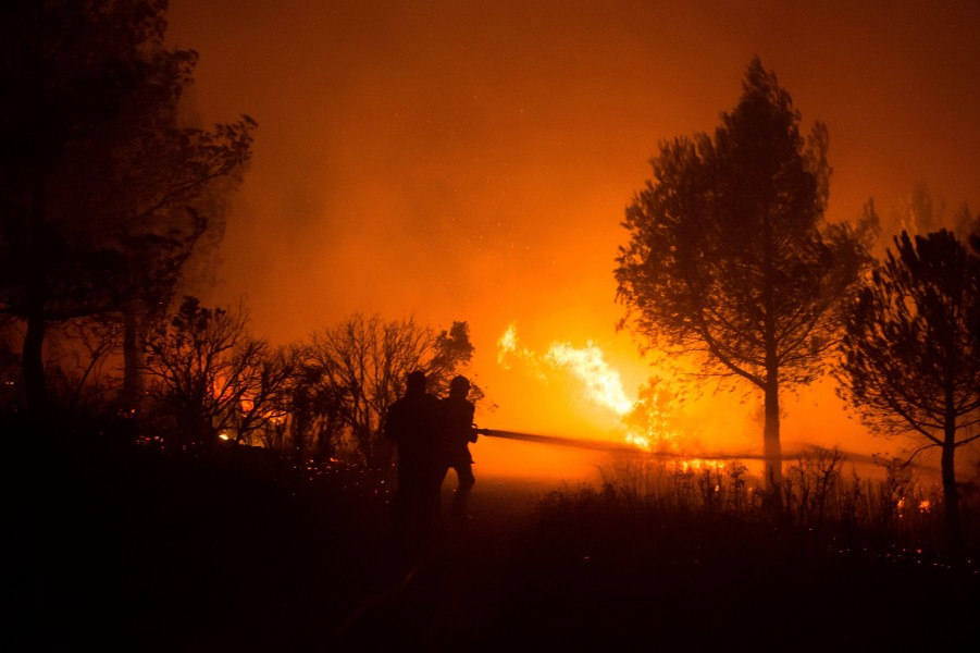 (FILES) This file photo taken on August 19, 2017 shows  firefighters working to put out a wildfire on a fire in Carnoux-en-Provence, southeastern France, on August 19, 2017. A 14-year-old teenager arrested on September 13, 2017 has confessed being responsible of several wildfires in the region of Marseille this summer, according to police sources on September 14. BERTRAND LANGLOIS / AFP