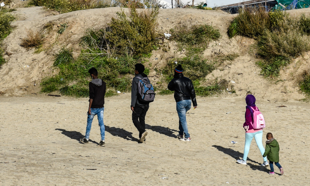 "Migrants walk through the ""Jungle"" migrant encampment in Calais on October 17, 2016, before the dismantlement of the site. Authorities have identified more than 7,000 places in shelters designed to accommodate migrants after the dismantling of the ""Jungle"" of Calais, according to an official document which AFP has received access."