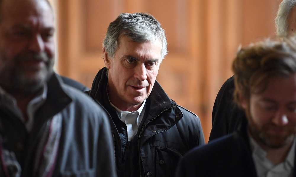 French former budget minister Jerome Cahuzac (C) reacts as he leaves, with his lawyers Eric Dupond-Moretti (L) and Antoine Vey (R), Paris' courthouse on February 21, 2018 on the last day of his appeal trial on tax fraud and money laundering.