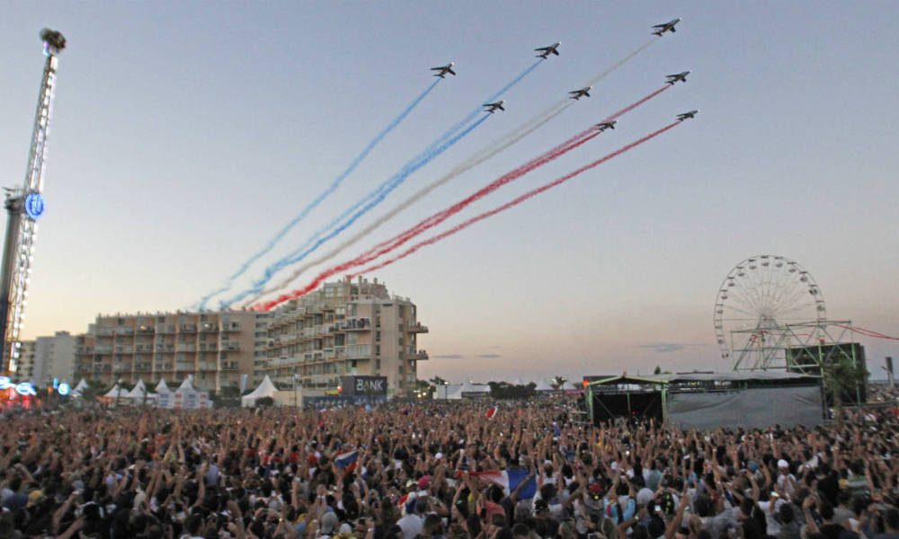 French elite acrobatic flying team Patrouille de France (PAF) release smoke in the colours of the French national flag above the first evening of the Electrobeach festival on July 14, 2016 in Le-Barcares, southwest France. Electrobeach, the largest electronic music festival in France, runs from July 14 to July 16.