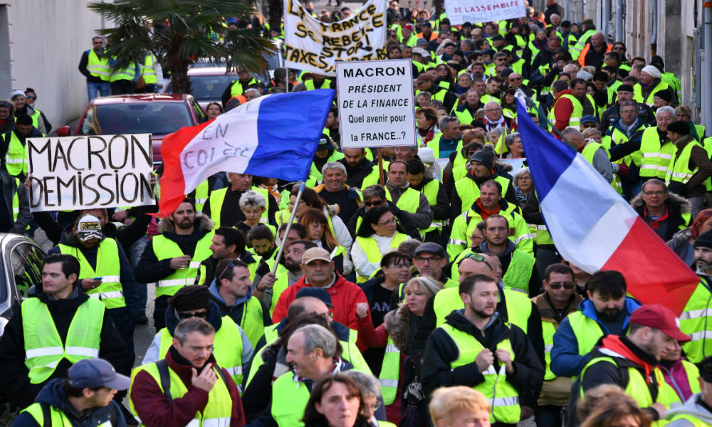 Yellow Vests (Gilets jaunes) shout slogans and wave placards as they participate in a protest rally against high fuel prices in Rochefort, south-western France on November 24, 2018, part of a movement which has mushroomed into a widespread protest against stagnant spending power under the French President.