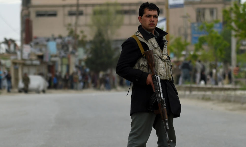 An Afghan policeman keeps watch near the site of a car bomb attack in the Puli Mahmood Khan neighbourhood in Kabul on April 19, 2016. A powerful Taliban car bomb followed by a fierce firefight left many people dead or wounded in Kabul April 19, the Afghan president said, a week after the insurgents launched their annual spring offensive.
