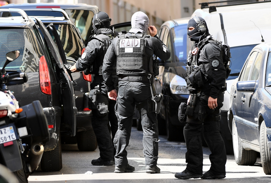"""Members of the French RAID police unit leave after searching the home of one of two men arrested in Marseille on April 18, 2017 after they were suspected of plotting an """"imminent"""" attack in France, days from presidential polls."""