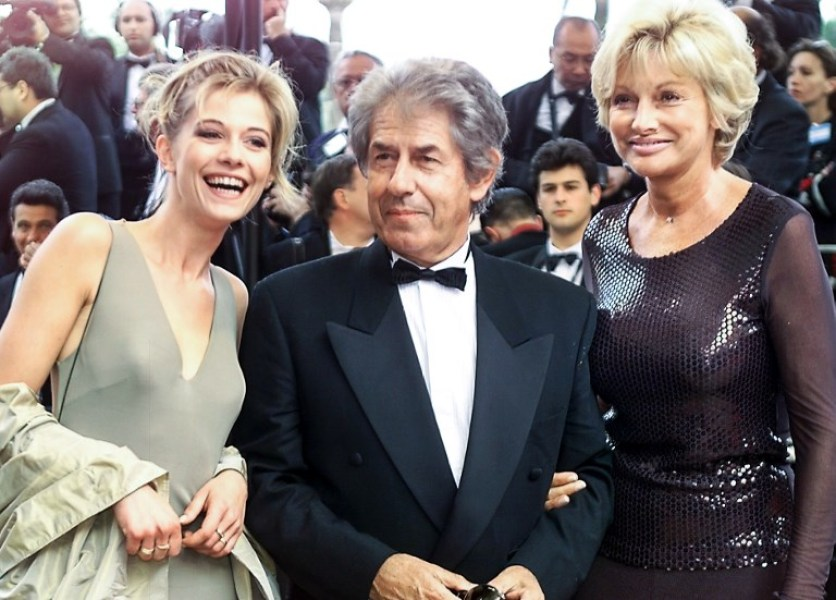 """n this file photo taken on May 14, 1999, French TV host Philippe Gildas (C), his wife Maryse (R) and Flavie Flament, then TV weather girl, pose on the steps of the Palais des Festivals before the screening of French filmmaker Leos Carax movie """"Pola X"""" in competition for the Palme d'or of the 52nd Cannes Film Festival in Cannes. Gildas has died on October 28, 2018 at the age of 82. MICHEL GANGNE / AFP"""