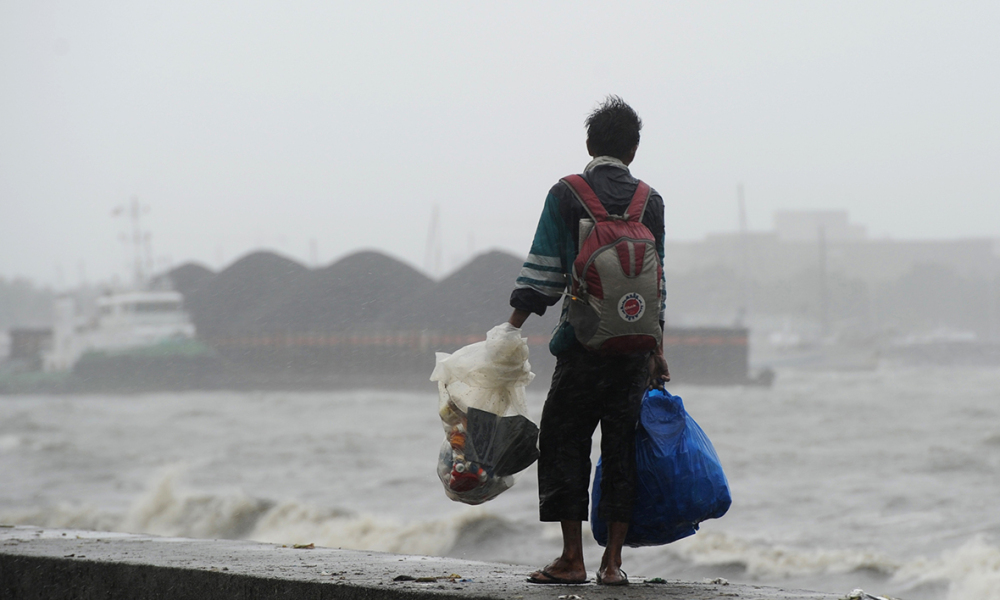 A man looks at a barge loaded with black sand after it was swept away during winds and rain brought on by typhoon Koppu, along Roxas boulevard in Manila on October 18, 2015, as the typhoon hit Aurora province, northeast of Manila. Powerful Typhoon Koppu ripped off roofs, tore down trees and unleashed landslides and floods, forcing thousands to flee as it pummelled the northern Philippines October 18, officials said