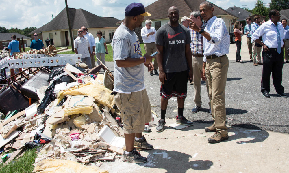 US President Barack Obama speaks with residents as he tours a flood-affected area in Baton Rouge, Louisiana, on August 23, 2016. President Barack Obama touched down in flood-stricken Louisiana Tuesday, hoping to offer support to devastated communities and silence his critics who say he should have visited sooner. NICHOLAS KAMM / AFP