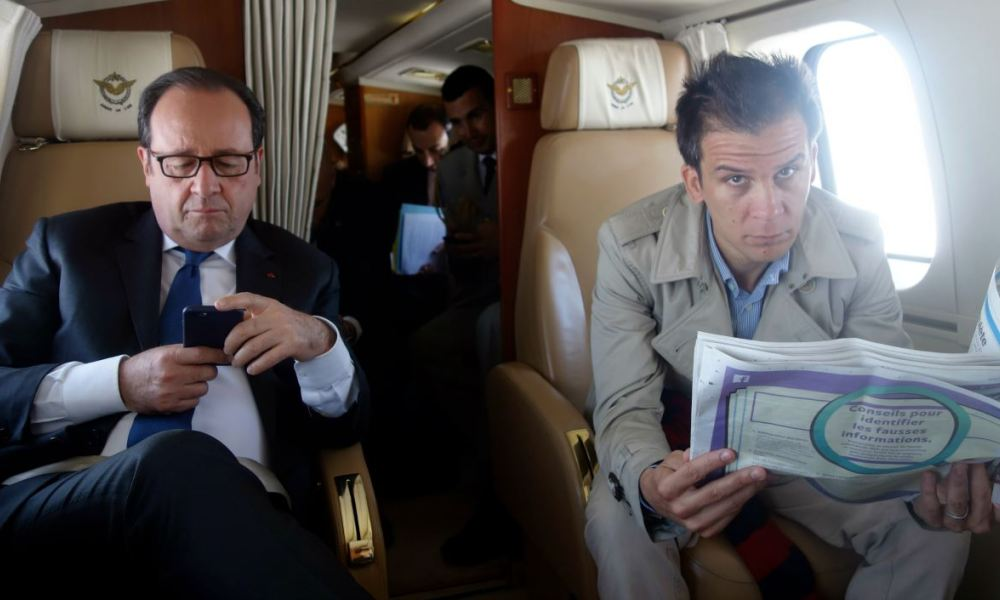 French President Francois Hollande (L) checks his mobile phone next to his press secretary Gaspard Gantzer in a helicopter between Niort and Paris on April 13, 2017.  Sabine WIBAUX / AFP