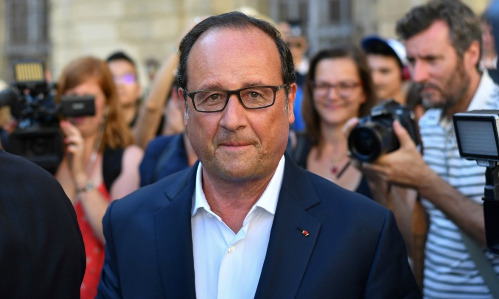 Former French President Francois Hollande (C) reacts as he leaves the City Hall in Arles, southern France, on July 21, 2017 before delivering his first speech since leaving the Elysee Palace as part the Napoleons innovative communications network. BERTRAND LANGLOIS / AFP