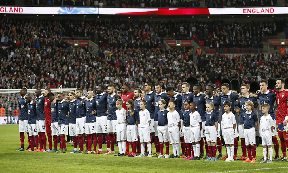 The France squad link arms before the start of the friendly football match between England and France at Wembley Stadium in west London on November 17, 2015.