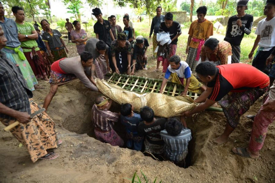 People burry an earthquake victim during a burial ceremony at Tanjung, in northern Lombok on West Nusa Tenggara province on August 10, 2018. At least 319 people died when a shallow 6.9-magnitude quake surged through the ground of the volcanic island to the east of Bali on August 5. SONNY TUMBELAKA / AFP