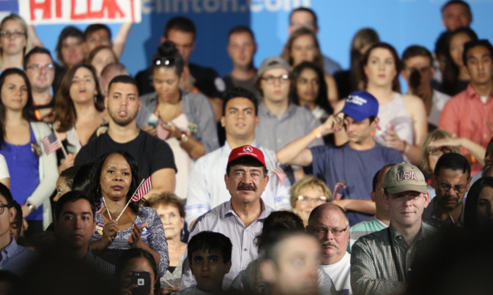 A man identified as Seddique Mateen (C-red ball cap), whose son shot and killed 49 people and injured 53 others inside the Pulse nightclub in June, sits with supporters at a rally for Democratic Presidential nominee Hillary Clinton at the Osceola Heritage Park in Kissimmee, Florida on August 8, 2016.  Gregg Newton / AFP