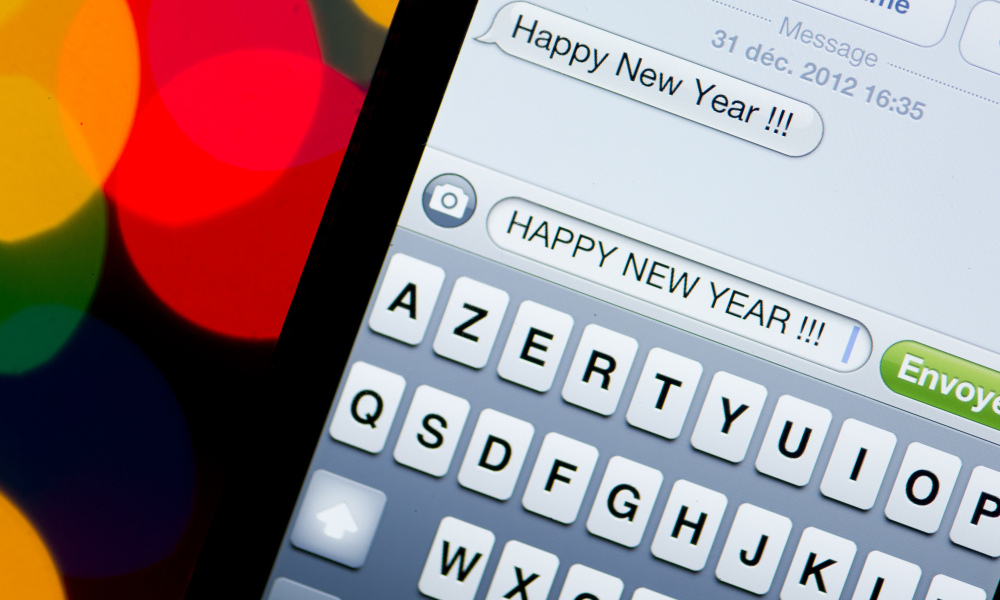 A text message (SMS) of New Year greetings in English is pictured on a smartphone on December 31, 2012 in Paris. Millions of SMS should be sent in the world on January 1, 2013. AFP PHOTO LIONEL BONAVENTURE LIONEL BONAVENTURE / AFP