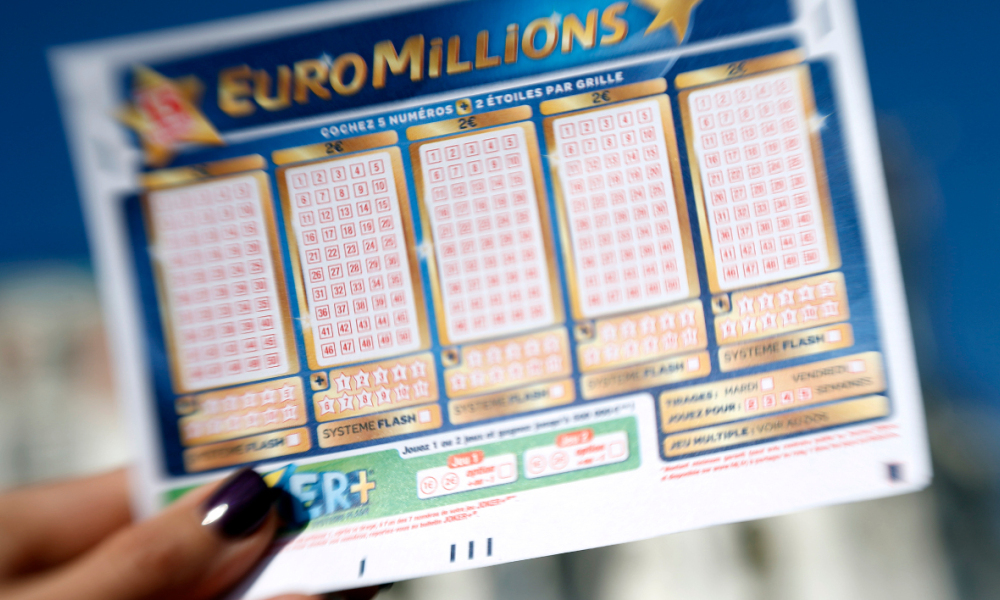 A person holds an Euromillions lottery ticket on november 14, 2012 in Nice. A lucky punter beat the French record for a Euromillions lottery today, winning a staggering 169,837,010 euros (almost $216 million), enough to buy nearly four tonnes of gold. The sole winner of the draw beats the former French record, won by a man in Calvados last year, by over seven million euros. AFP PHOTO / VALERY HACHE VALERY HACHE / AFP