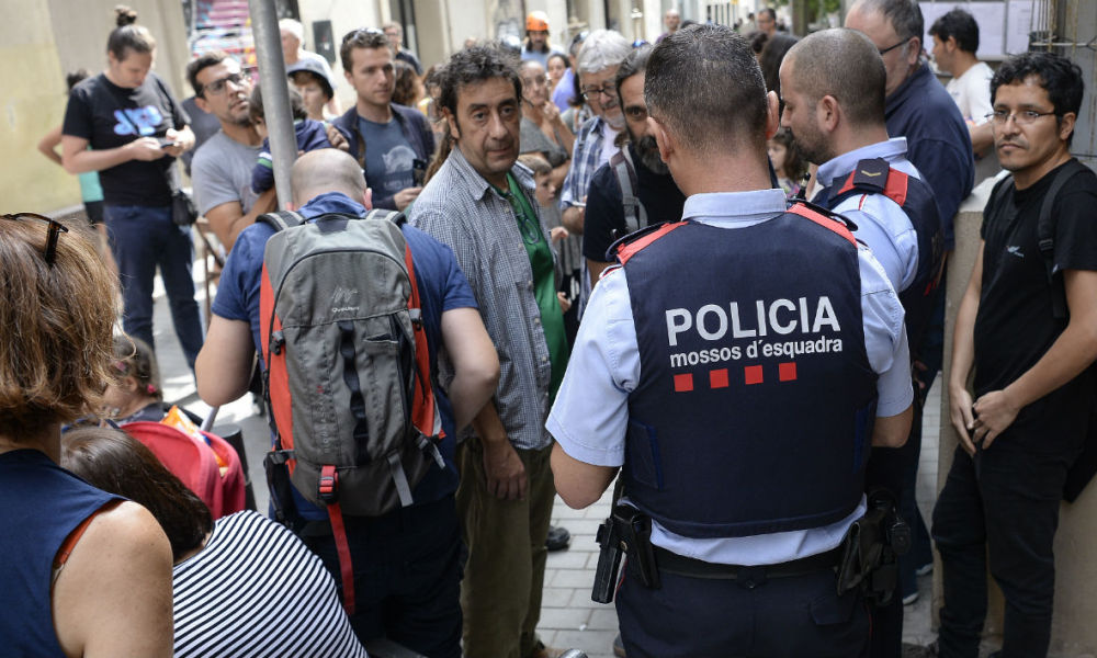 Catalan police officers report the activities organized by parents in a school at the Gracia neighbourhood in Barcelona, on September 30, 2017. Supporters of an independence referendum in Catalonia opposed by Madrid occupied would-be polling stations yesterday in a bid to ensure the vote goes ahead, as thousands gathered in Barcelona for the separatist camp's closing campaign.  Josep LAGO / AFP
